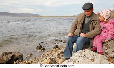 daddy with daughter sit on stone on riverbank, look afar and...