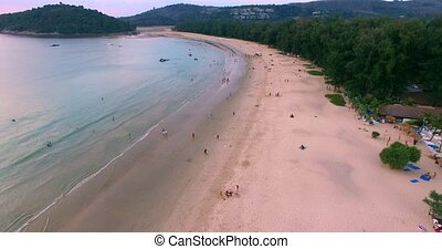 Aerial footage. Flying close over tropical sandy beach and...