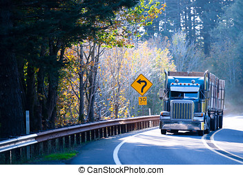 Blue classic semi truck rig with trailer on sunny windy road