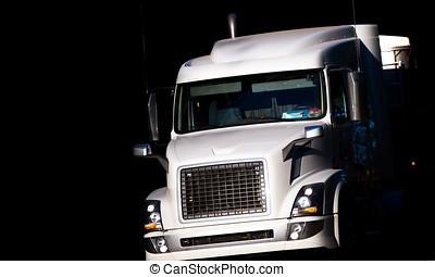 Modern big rig white semi truck in dark shadow