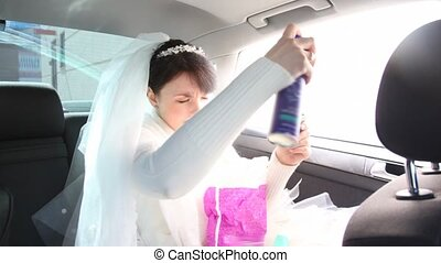 bride hairdressing by hairspray in car - bride with hand...