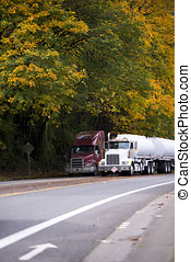 Two big rigs semi trucks with trailers on autumn road with yellow trees