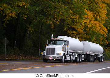 White big rig semi truck with two tank trailers on autumn road
