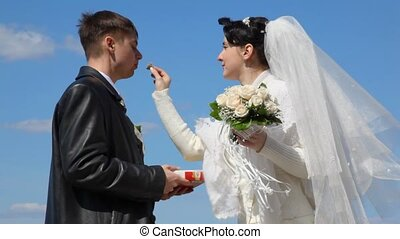 bride feeds with sweets her groom - bride with bouquet feeds...