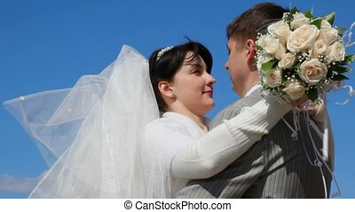 bridegroom and bride kissing outdoor, blue sky in background
