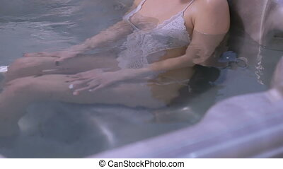 Female friends relaxing in jacuzzi, speaking and smiling....