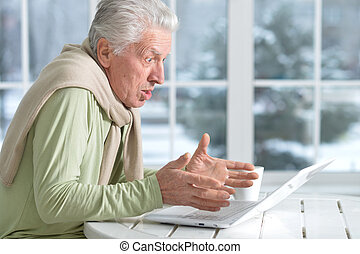senior man using laptop sitting near window