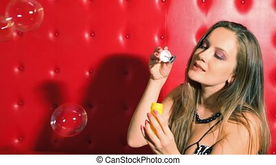 girl blowing soap bubbles indoor on red background