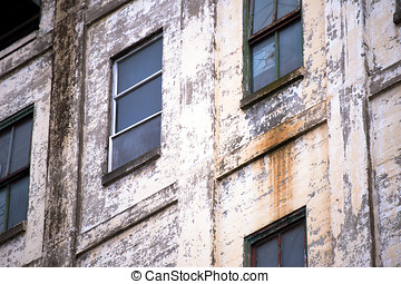 Wall of the old industrial building with windows and shabby...