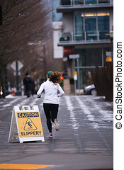 Woman runner running in the street of urban city - A woman...