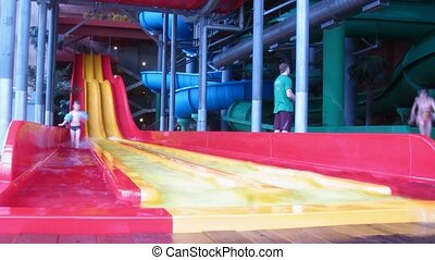 People slide from slide in an aquapark, blured faces -...