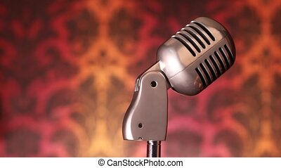 female hands laying on microphone on rack with reflection of...