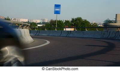 black cars moves on highway with road sign in city - two...