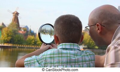 father and son stands on bank of river and looks through magnifying glass
