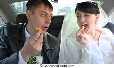 bridegroom and bride sits in car and eats baked goods -...