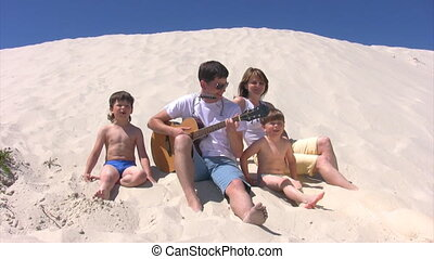 singing family with guitar and harmonica sits on beach -...