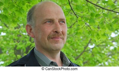 bald-headed man with moustache stands under tree - portrait...