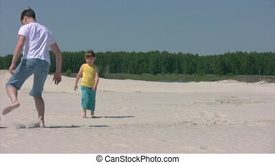 man and boy plays football on beach - young man and little...