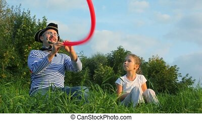 man in pirate costume giving air balloon to girl - man in...