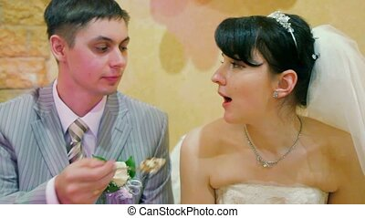 bridegroom feeding bride at wedding table - bridegroom...