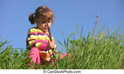 girl sits on meadow and stirs ground and grass by stick