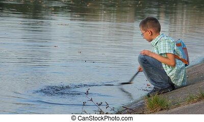 boy sitting on coast and beats by stick on water surface -...