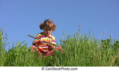 girl sits on meadow and stirs grass and ground by stick