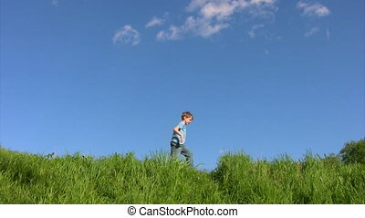 boy walking on grass in field under sky