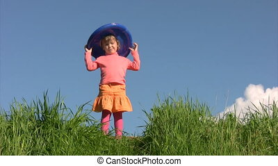 girl in american flag hat stands on field against sky