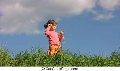 girl sticking flowers in her hair, stands against sky