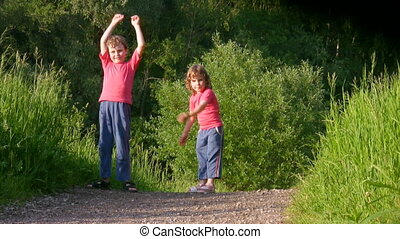 boy and little girl exercising in forest