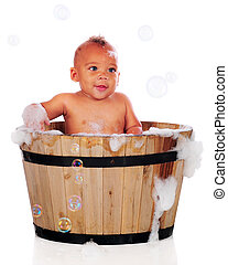 Bubble Bath Baby - An adorable biracial baby bathing with...