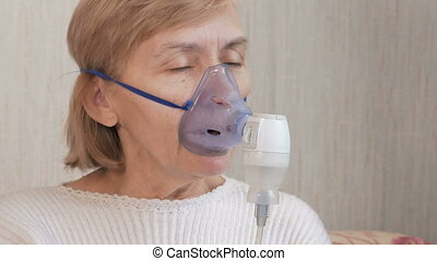 Senior woman holding a mask from an inhaler at home. Treats...