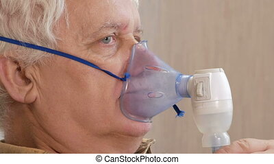 An elderly man holding a mask from an inhaler at home....