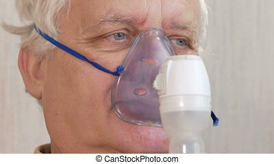 An elderly man holding a mask from an inhaler at home. Treats inflammation of the airways via nebulizer. Preventing asthma and cough. Close-up.