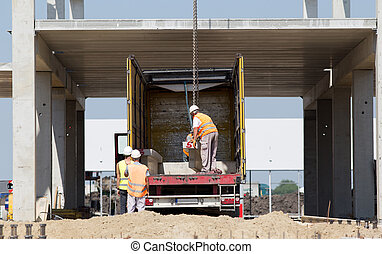 Crane lifting truss - Workers mounting concrete truss on...