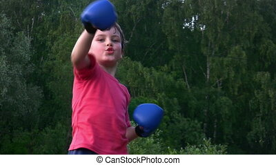 boy in boxing gloves exercising karate in park - boy in...