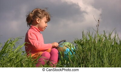 girl with terrestrial globe sits on grass against sky -...