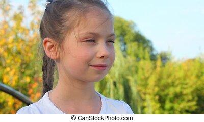little girl standing against trees in park