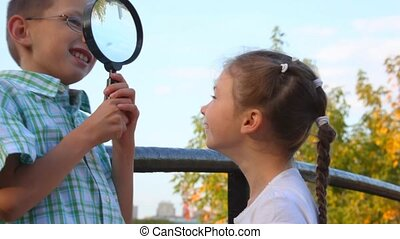 boy and little girl plays with magnifying glass outdoor