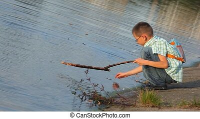 boy sits on coast and beats by stick on water surface - boy...
