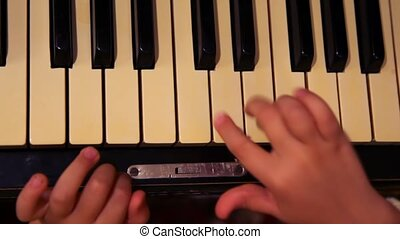 childrens hands pressing keys of piano - close up childrens...