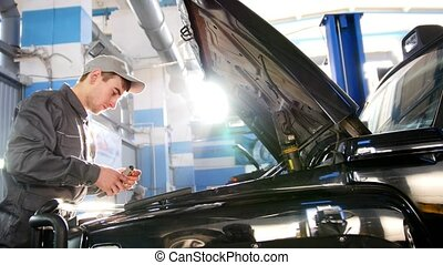 Mechanic male in automobile garage checking hood of the car...
