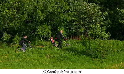 father with son and mother riding bicycles in park - father...