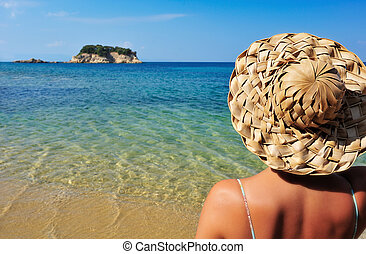 Young woman in hat looking at small island - Closeup image...