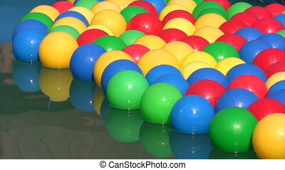 balls floating in inflatable swimming pool - multicolored...