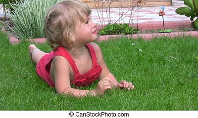 little girl lying on green grass in outlet - portrait of...