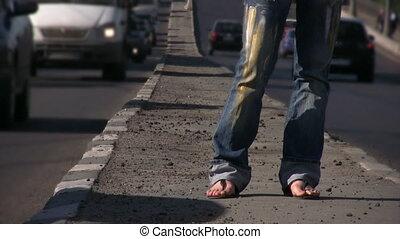 feet of girl standing on highway middle in city
