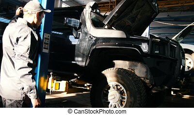 Mechanic lifts SUV in garage automobile service, close up