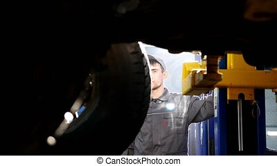 Mechanic lifts SUV in garage automobile service - wheel,...